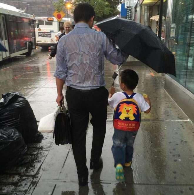 Il papà si bagna per proteggere il figlio dalla pioggia: in realtà sta facendo molto di più